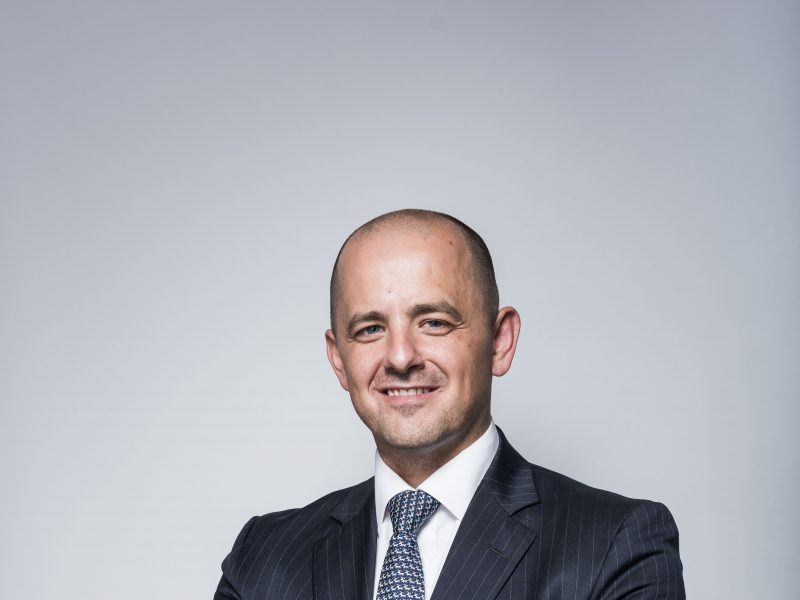 Evan McMullin smiling with gray backdrop